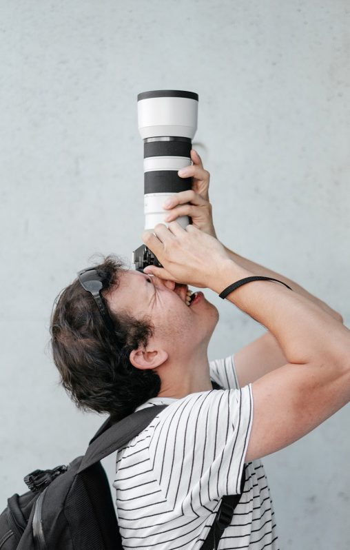 A man with a long zoom lens