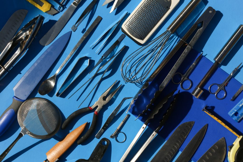 A selection of professional food styling equipment including knives, whisks, tongs and sifters